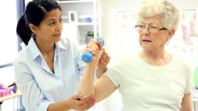 vídeos de stock, filmes e b-roll de fisioterapeuta trabalha com mulher sênior na reabilitação - fisioterapeuta