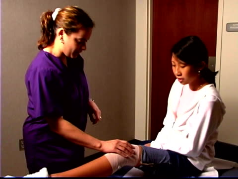A physical therapist wraps a girl's knee with an ace bandage and checks for mobility.