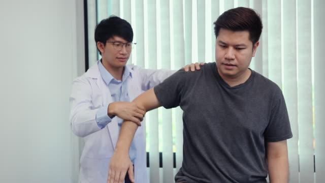 vídeos de stock, filmes e b-roll de fisioterapeutas pressionam o ombro do paciente para verificar a dor. - physical injury