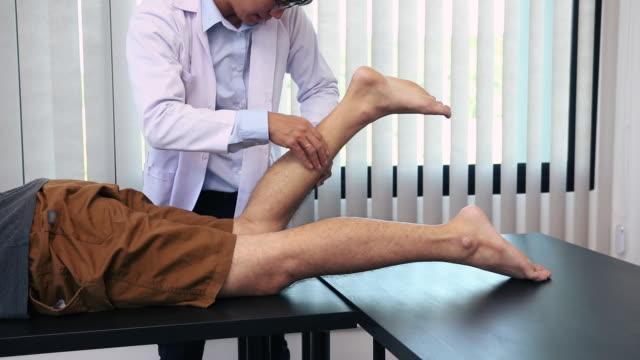 vídeos de stock, filmes e b-roll de fisioterapeutas usam as mãos para verificar os músculos da panturrilha. - brace