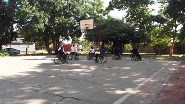 physically challenged african wheelchair basketball players warming up for a match - avvenimento sportivo video stock e b–roll