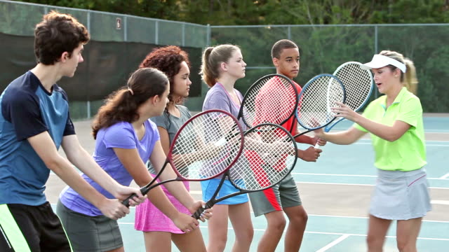 Physically challenged teenager in group tennis lesson