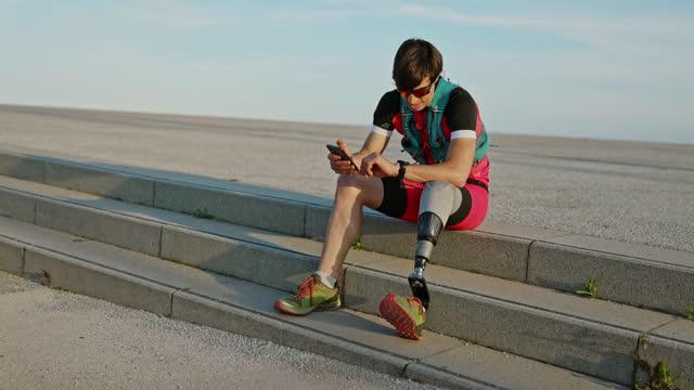 vídeos y material grabado en eventos de stock de atleta con discapacidad física tomando un descanso con el teléfono inteligente - vida real