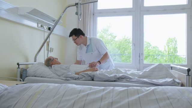physician interacting with elderly patient in hospital ward - medical building stock videos & royalty-free footage