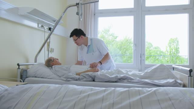vídeos y material grabado en eventos de stock de médico que interactúa con un paciente de edad avanzada en la sala del hospital - visita