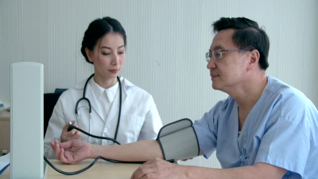 Physician measuring female patient blood pressure at hospital