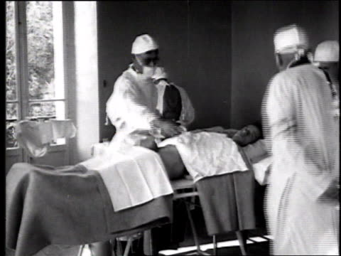 physician shaving abdomen of patient on table, nurse standing at patients head and another medical person standing nearby observing / france - 1918 stock videos & royalty-free footage