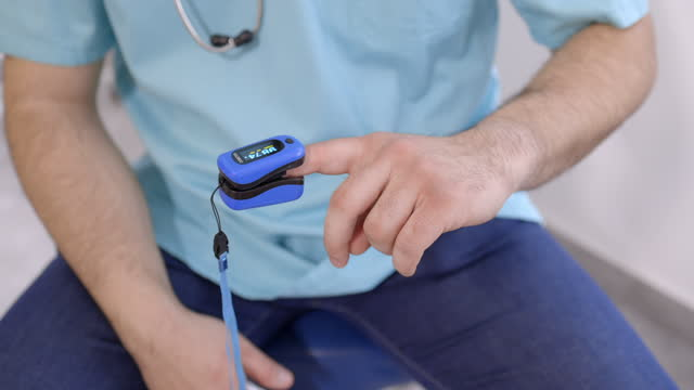 physician testing blood saturation instrument - oximeter with display - index finger stock videos & royalty-free footage