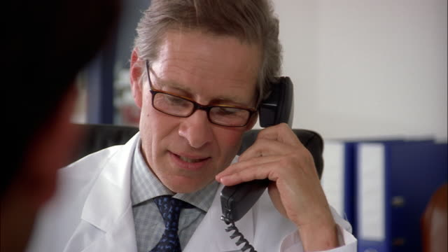A physician wearing eyeglasses and a white lab coat talks on a telephone and chats with a patient in his office.