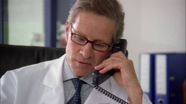 A physician wearing eyeglasses and a white lab coat talks on a telephone.