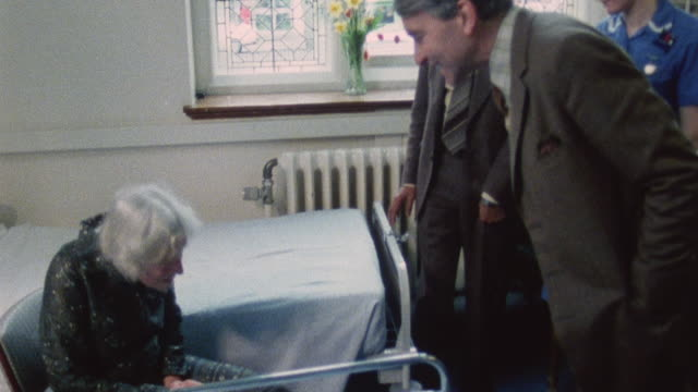1983 montage physicians and nurse talking with elderly patient in hospital / minehead, somerset, england - minehead stock videos & royalty-free footage
