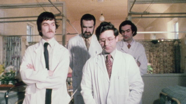 1970 DS Physicians making rounds and discussing patients in hospital ward / London, England