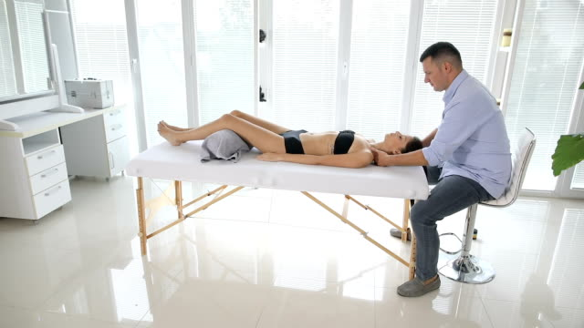 vídeos de stock e filmes b-roll de physiotherapist doing thorax manipulation on woman. - reiki