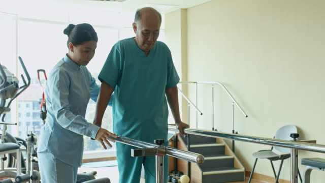 Physiotherapist helping senior man using walking bars at rehab