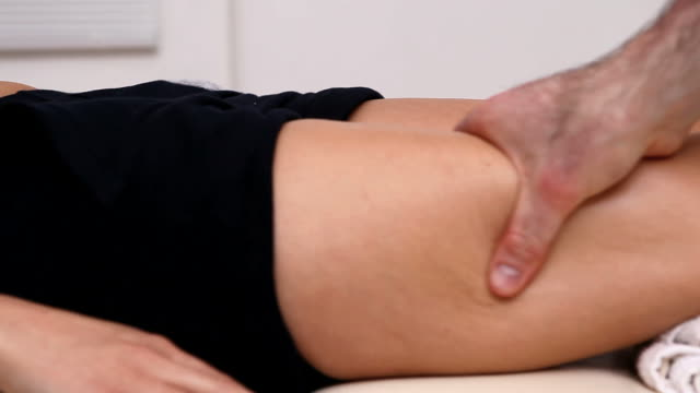 Physiotherapist massaging the thigh of someone