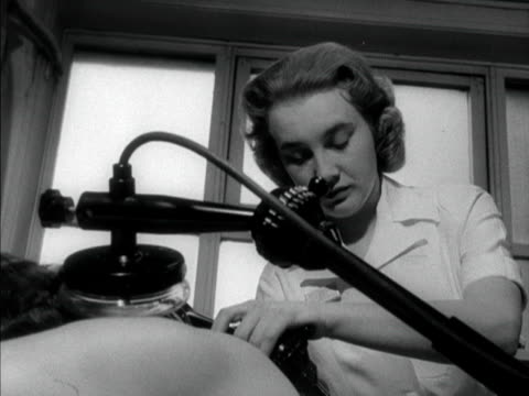 physiotherapist places a machine onto the shoulders of a female patient. 1958. - patientin stock-videos und b-roll-filmmaterial