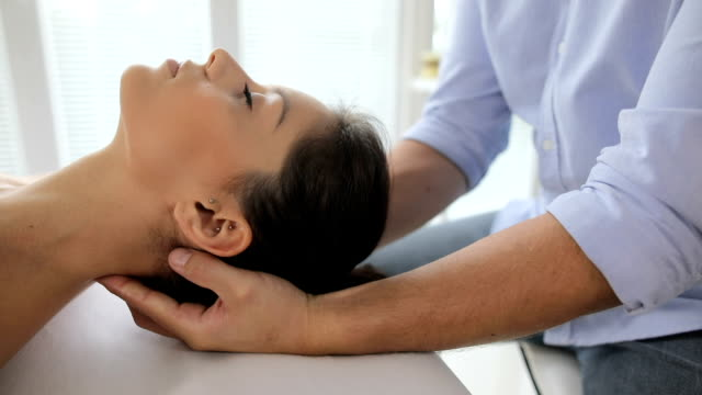 physiotherapist pressing back of womans head - osteopath stock videos & royalty-free footage