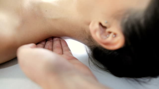 physiotherapist pressing back of womans neck - chiropractic adjustment stock videos & royalty-free footage