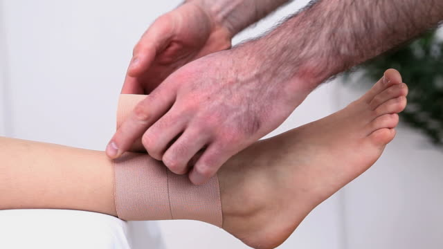 Physiotherapist strapping the ankle of a woman