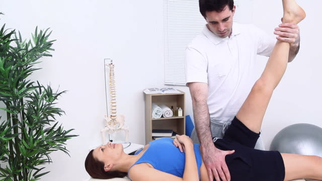 Physiotherapist stretching a leg of a woman