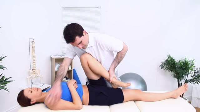 Physiotherapist stretching the leg of a lying patient