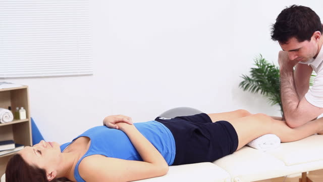 Physiotherapist using his elbow to massage a woman