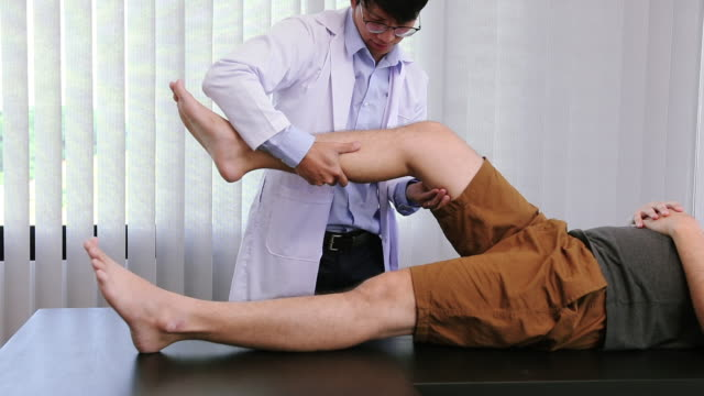 physiotherapists are using the hands to grip the patient thigh to check for pain and massage in the clinic. - thigh human leg stock videos & royalty-free footage