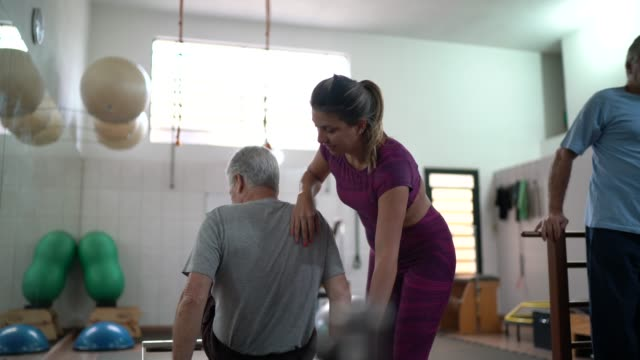 physiotherapy instructor and patient in yoga studio - chiropractic adjustment stock videos & royalty-free footage