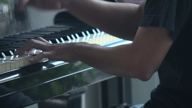 vídeos de stock e filmes b-roll de pianist playing grand piano with cinematic stage lighting - pianista