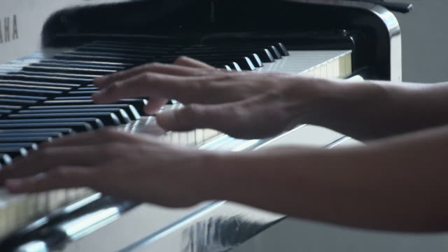 vídeos de stock e filmes b-roll de pianist playing grand piano with cinematic stage lighting - piano