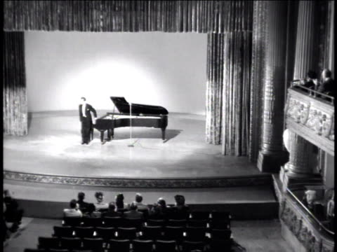 vídeos de stock e filmes b-roll de 1947 ha pianist sitting down at grand piano on stage - pianista
