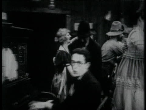 vídeos de stock e filmes b-roll de 1919 ms piano player makes music and couples dance in old west saloon - 1919