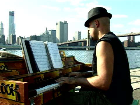 piano serenades have now joined the discordant symphony of traffic and blaring sirens on the streets of new york. new york, new york, united states. - orchestra sinfonica video stock e b–roll