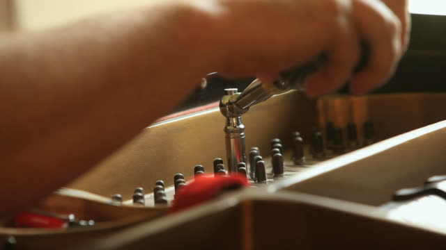 cu focus piano tuner using a tuning hammer to adjust pins on a grand piano/ chelsea, michigan, usa - ピアノ点の映像素材/bロール