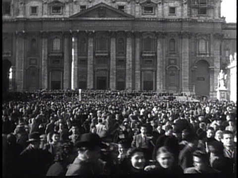 piazza san pietro filled w/ people standing walking two priests looking in vatican newspaper w/ headline 'anno santo' above photo of pope pius xii... - priest stock videos and b-roll footage
