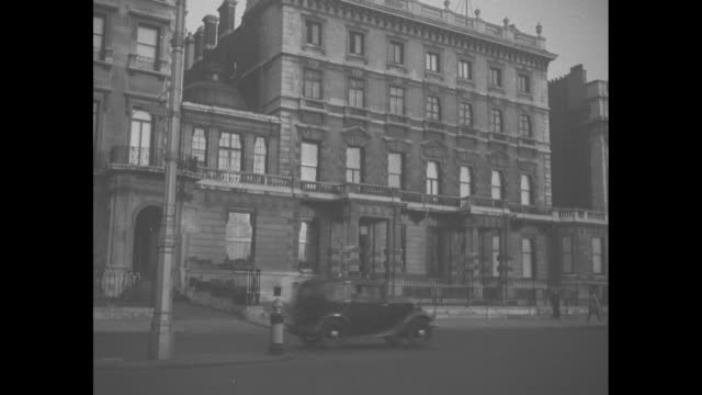 145 piccadilly the home of prince albert duke of york / person exits car and enters house / people gathered at fence / princesses elizabeth margaret... - abdication stock videos and b-roll footage