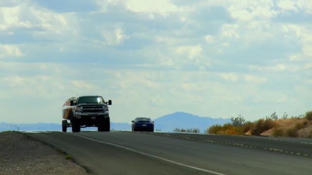 stockvideo's en b-roll-footage met ws, pick up truck pulling boat on trailer on desert highway, nevada, usa - aanhangwagen