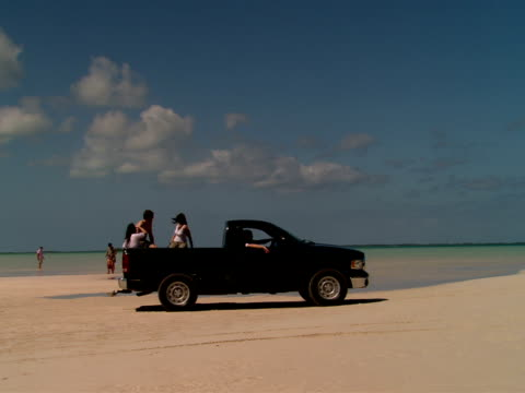 MS,  TS,  pick up truck with people on back driving on beach