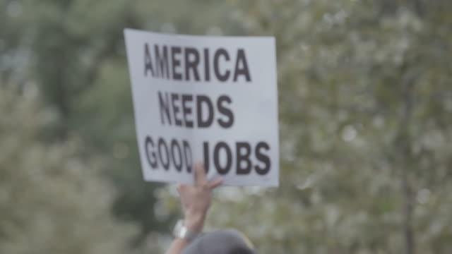 picket skyltar som transporteras genom staden gatan. - arbetslöshet bildbanksvideor och videomaterial från bakom kulisserna