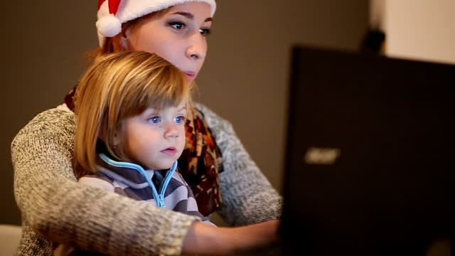 vídeos de stock e filmes b-roll de picking new year's program for my lovely boy - chapéu do pai natal