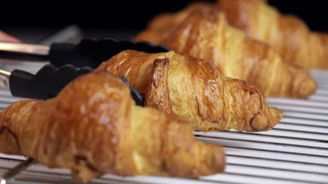 abholung eines frisch gebackenen croissants vom kühltablett - türkei stock-videos und b-roll-filmmaterial