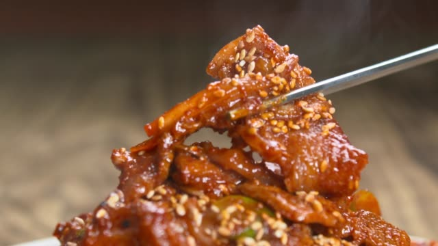 picking up a piece of jeyuk-bokkeum(stir-fried spicy pork with chopsticks - spice stock videos & royalty-free footage