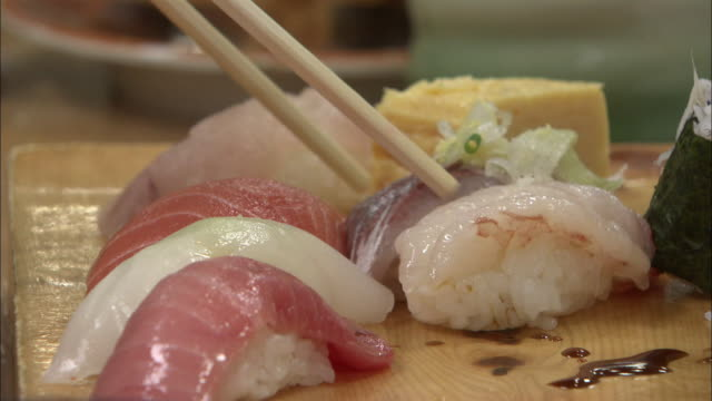 picking up a sushi with chopsticks in tokyo, japan - fish stock videos & royalty-free footage