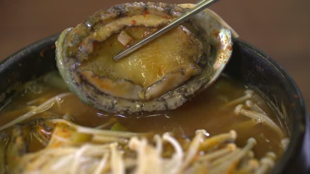 Picking up an abalone with chopsticks (Korean food)