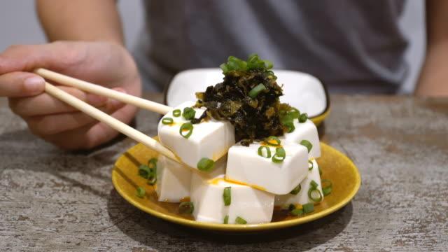stockvideo's en b-roll-footage met gekoelde tofu sashimi oppakken via stokjes - blok vorm