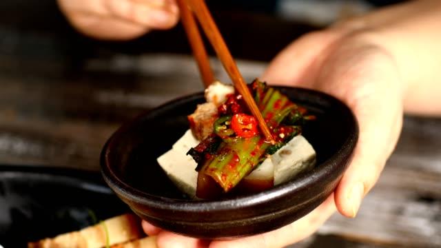 Picking up gat (leaf mustard) kimchi, tofu and boiled pork with chopsticks
