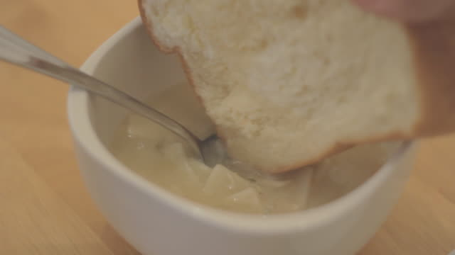 picking up pieces of bread from plate and dipping them into bowl chicken noodle soup. - dipping stock videos & royalty-free footage