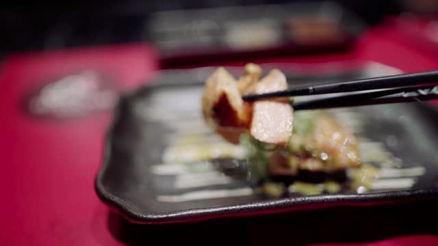 picking up salmon steak with chopsticks in japanese food restaurant - salmon steak stock videos & royalty-free footage