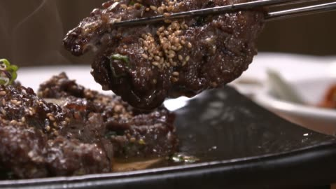 vídeos y material grabado en eventos de stock de picking up tteok-galbi(grilled short rib patties) with chopsticks - comida coreana