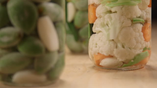 pickled almonds rackfocus on glass jars filled with pickled almonds with garlic and pickled cawliflower - cauliflower stock videos & royalty-free footage
